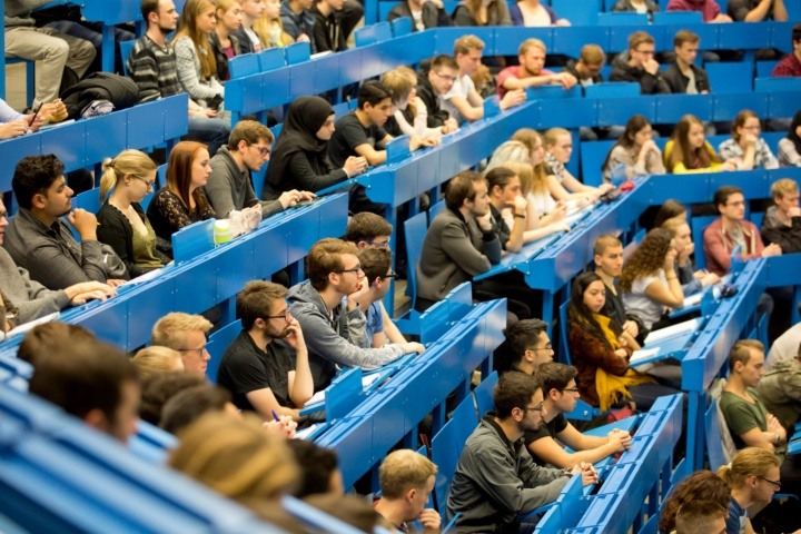 Students sit on the blue benches of a lecture hall and look forward attentively.